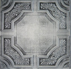 An ornate wall or ceiling panel made from Styrofoam that is hand painted to look like Antique Silver