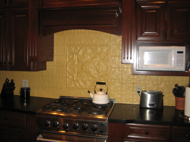 Dark wooden cabinets with creamy, Aluminum backsplash tiles and a medallion as a center piece.