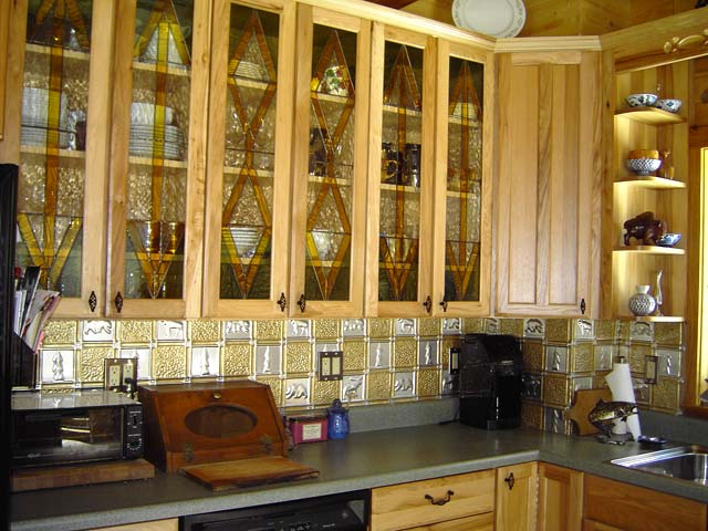 kitchen cabients with stained glass and 2 color backsplash