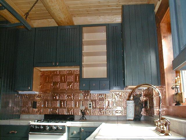 Blue cabinets with redish backsplash