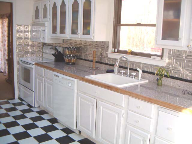 Light wood kitchen cabinets with clear coated aluminum backsplash.