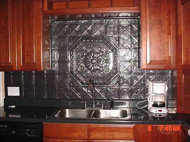 Semi dark kitchen cabinets with a tin backsplash tiles and a medallion as a center piece over a sink.