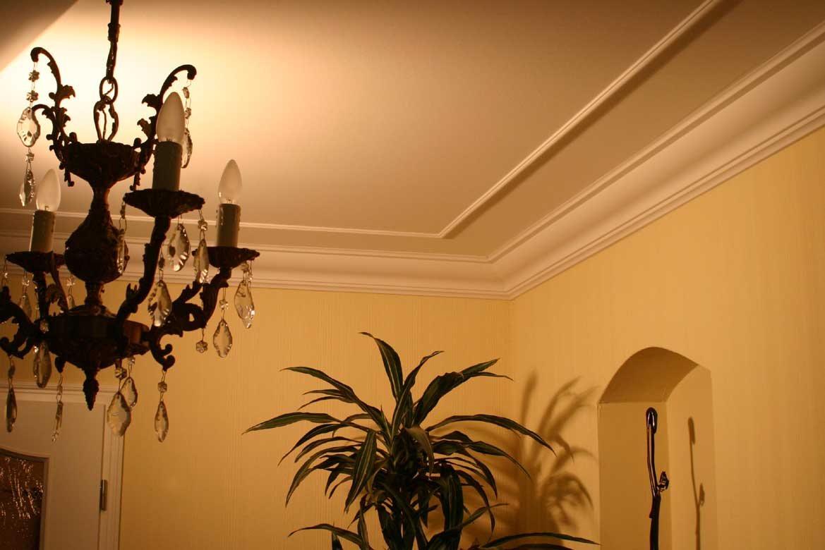 ceiling with a classic chandelier, crown molding and a trim.