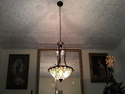 204 White Matte Ceiling Tiles installed on a ceiling with a chandelier and it looks like arround Christams time too.