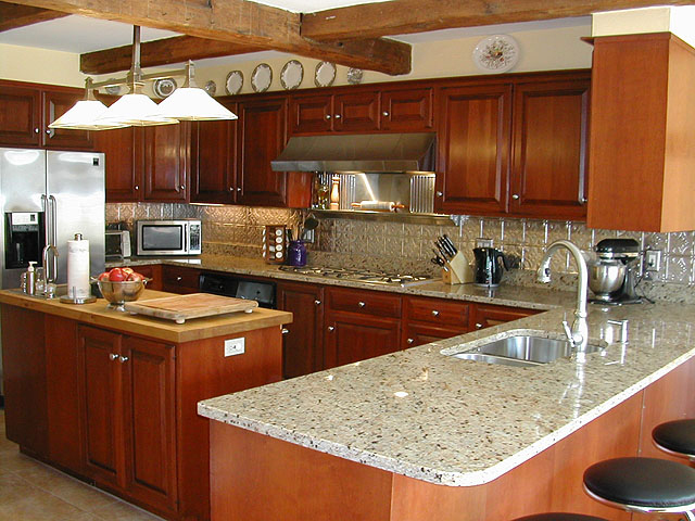 Lovely kitchen with an island, medium dark stained cabinets, Stainless Steel Aplicances and matching backsplash.