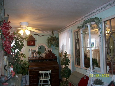 Before image of an Living Room with green walls, big window and a hardwood floor.