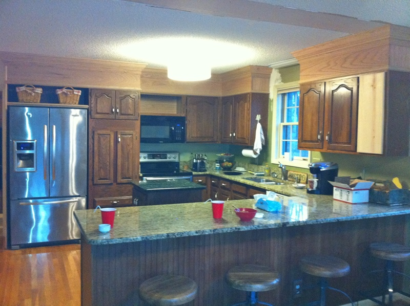 Before shot of a kitchen with dark oak cabinets and popcorn ceiling.