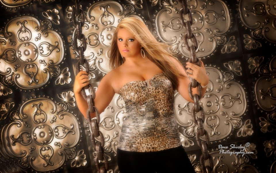 blond-senior-girl-holding-chains-infront-of-a-photography-backdrop.jpg