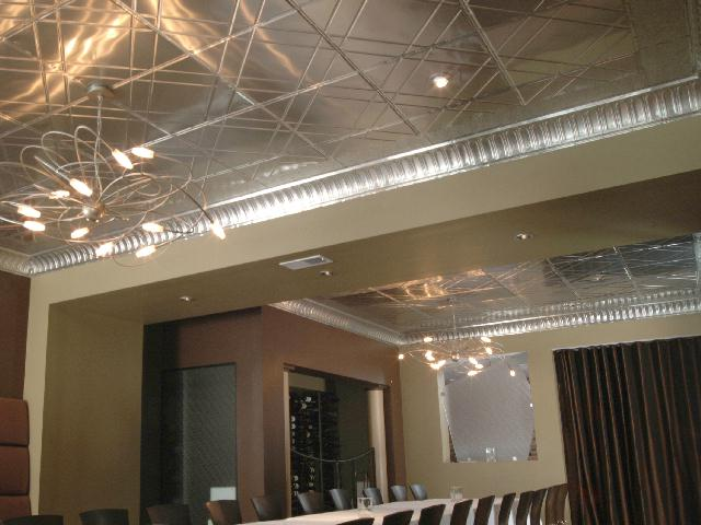 Contemporary ceiling tiles installed in a conference room with modern light fixtures.
