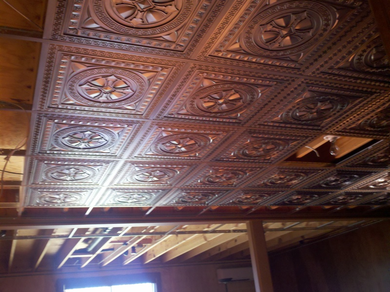 Basement Ceiling is getting some face-lift before the Super Bowl with antique copper ceiling tiles inserted into a suspended ceiling.