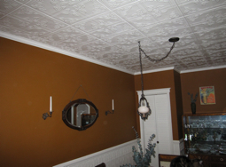 Dining room with brown walls, decorative ceiling tiles and wainscoting.