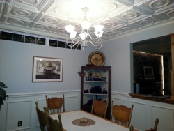 Beautiful dining room with white ceiling tiles and wainscoting.