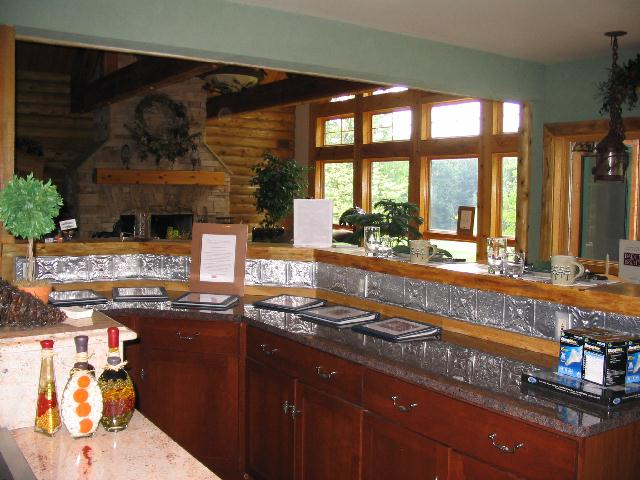Green walls, natural wooden trim and Aluminum backsplash are the features of this kitchen.