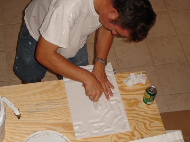 milan jara is applying ceramic tile adhesive on a foam ceiling tile r28.jpg
