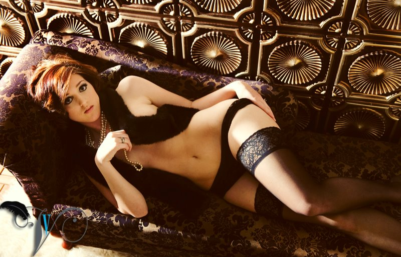Girl on a sofa in lingerie and pearls arround her neck photographed agains a photography backdrops made from faux tin ceiling tiles.