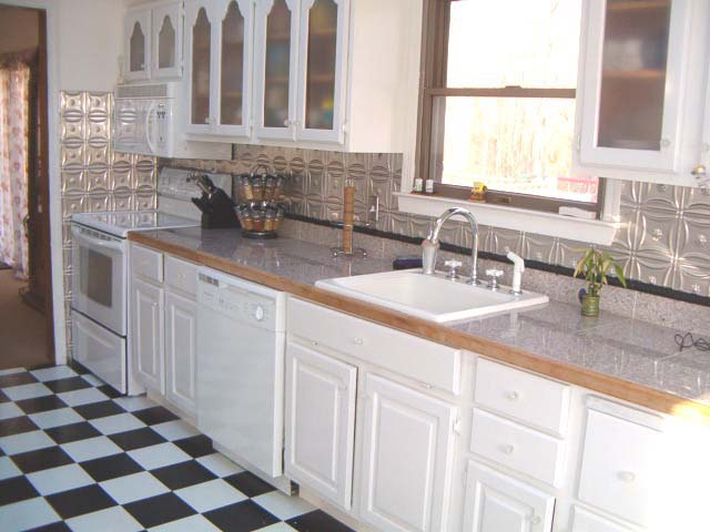 White cabinets with glass inserts, metal backsplash and a checkered white and black flooring are the features of this kitchen.