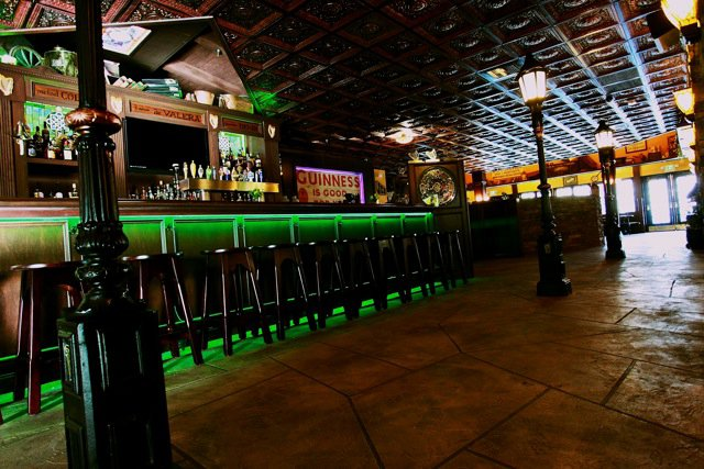 Irish pub and restaurant with rich irish decor, featuring coffered ceiling tiles, lamp posts inside and decorative concrete flooring.