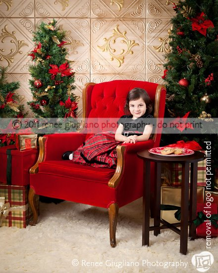 Christmas photography set with a red chair, two christmas trees and styrofoam ceiling tiles painted gold as a backdground.