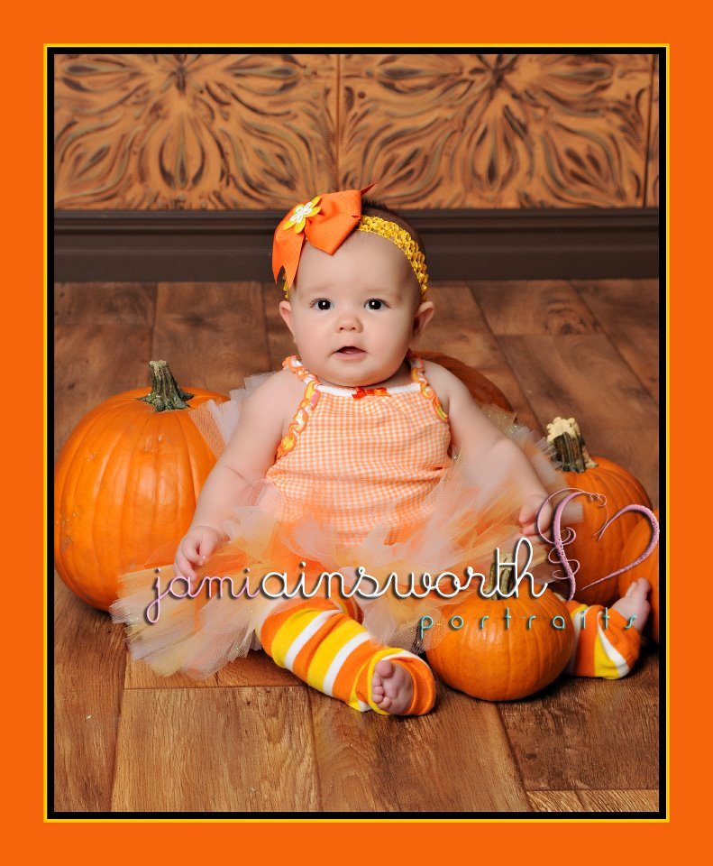 Baby girl with pumpkins infront of a brown photography backdrop