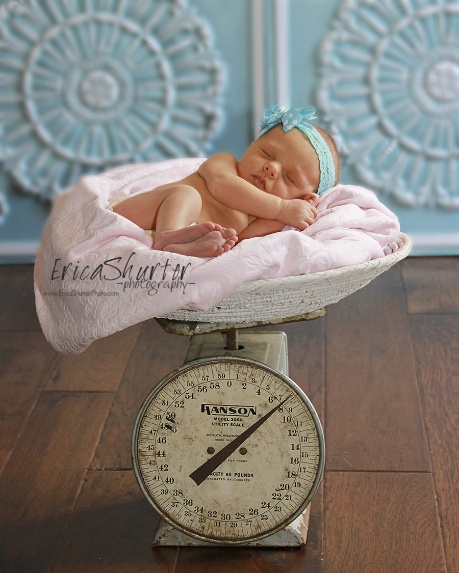 Sleeping baby on in the blanket on top of a vintage scale with blue photography backdrops.